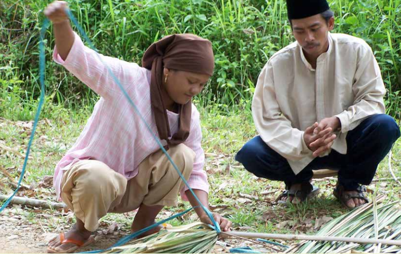 Photo: A woman in Jambi, Sumatra, showing a man how she prepares forest fibers for weaving. Carol Colfer/CIFOR