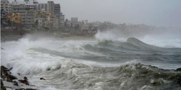 City on coast to the left of the image, strong waves on the right