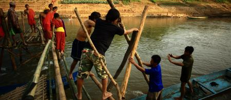 Residents repair a damaged bridge in Lao PDR