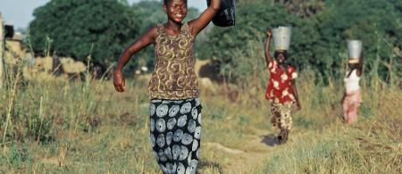 village women carry containers full of water from the well
