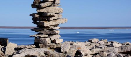 A inukshuk uphill from Igloolik, Nunavut, Canada. About 5 feet tall and made of flaggy dolomite.