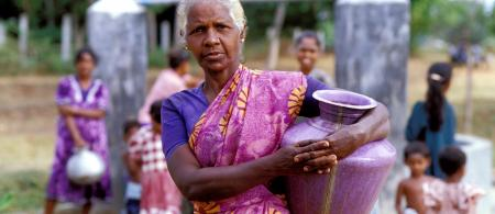 Woman with water container at well. Sri Lanka. Photo © Dominic Sansoni / World Bank