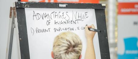 Facilitator writes the advantages of alignment on a flip board chart.
