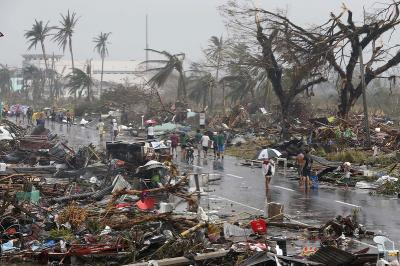 Residents walk on a road littered with debris after Super Typhoon Haiyan battered Tacloban city in central Philippines November 10, 2013