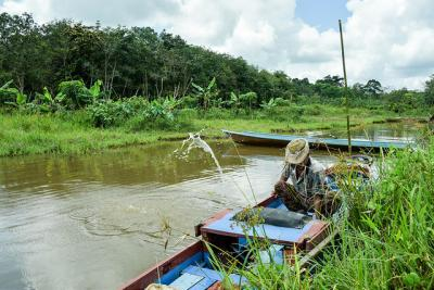 Man in boat fishes in river
