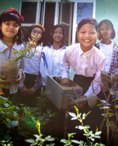 group of girls and boy tending garden