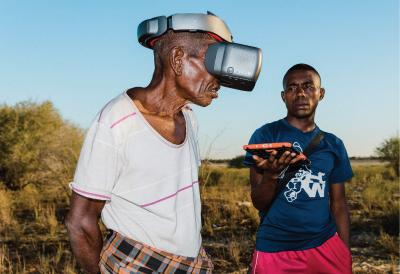 Blue sky, a man has a virtual reality mask, another man holds a tablet while looking at the first man..