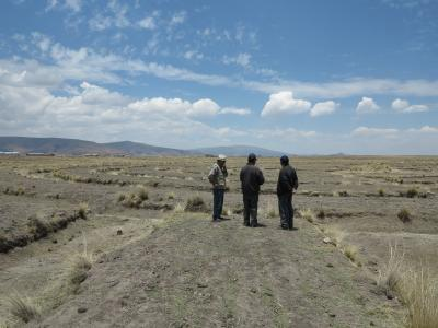 The picture shows a farmer with staff from the weather service in front of dry farmland