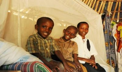 Three boys test a new bed net provided through a partnership of the NGO Malaria Consortium and the Government of Mozambique.